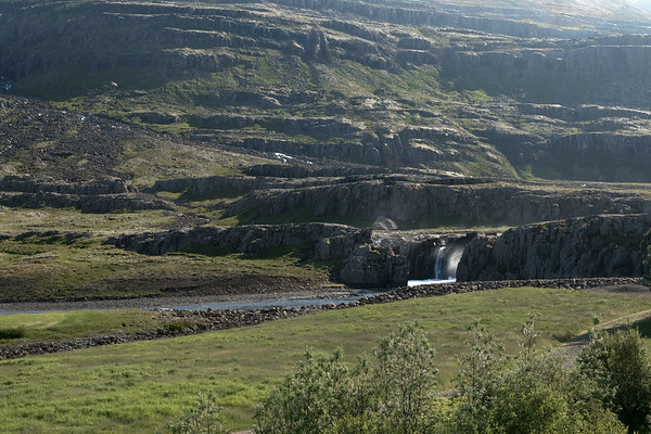 Falls along the Fossárdalur (valley) - sourced by the Fossá (river) - with the volcanic rock ledges along the northern slope of the Afrettarfjall  (mountain) beyond - here in the northwestern area of the Berufjörður (fjord) - Eastern region of Iceland.