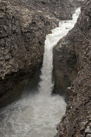 A plunge or vertical falls, descending the Far (river), amongst the mostly barren volcanic basalt rock - Central Highlands - Southern region of Iceland.