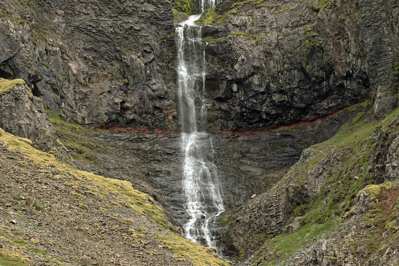 Cascade falls amongst the igneous basalt rock, including a thin strata of iron oxide, and clustered with moss, lichen, grass, and heath vegetation - located along the slope of the Skápadalsmúli  Mountain - the eastern end of the Osafjörður (fjord) - Westfjords region of Iceland.