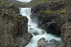 Sveinsstekksfoss (falls) - Fossá (river) - volcanic rock, lichens, moss, and grass.