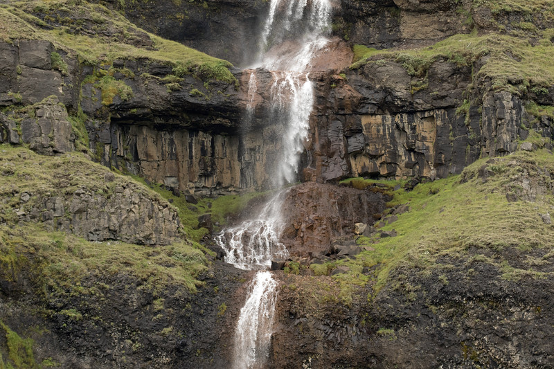 Merkilækur (stream) Falls - cascading amongst the volcanic basalt rock, clustered with moss, lichen, and grass of the Boreal Birch Forest ecoregion.