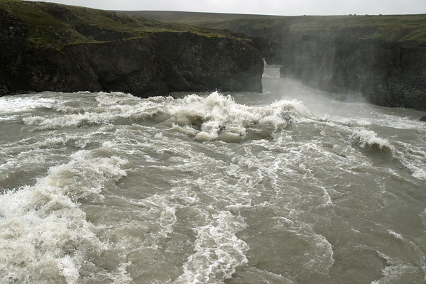 Gýgjarfoss - over the crest which measures about 65 ft. (20 m) across, then dropping about 20 ft. (5 m), and into the volcanic rock canyon along the Jökulfall (a glacial sourced river) - Central Highlands area, of the Central region in Iceland.
