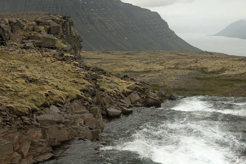 Over the crest of a falls along the Dynjandisá (river), adjacent the moss clustered igneous rock - beyond to the slope of the Urdarfell (mountain) and a few snow patches thereupon, during early July - and below the Arnarfjörður (fjord), with distal the glacial slopes of the Slettanes (peninsula) - Westfjords region of Iceland.