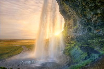 Sun setting through Iconic Seljalandsfoss waterfall, Southern Iceland