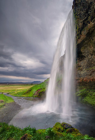 Seljalandsfoss  During my Icelandic adventure with Colby Brown, Ken Kaminesky and a team of awesome fellow photographers, we made close encounters with dozens of beautiful waterfalls. Although they were all somewhat similar (I mean, water that falls from cliffs), each of them was nothing short of breathtaking!  Seljalandsfoss is located in Southern Iceland and is one of the most famous Icelandic waterfalls. The river cascades 62 meters off the cliff edge. It is very picturesque and is famous since a small footpath makes possible for the visitor to go behind the waterfall. But if you ever want to try that, don't forget your raincoat! Indeed, the mist that is created by the falling water is very intense and you'll get drenched in just a few seconds!