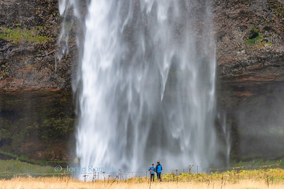 A couple admiring the Iconic Seljalandsfoss waterfall, southern Iceland