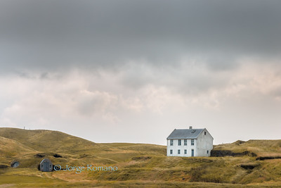 White Icelandic farm house with grass roof shed on a cloudy day in Southern Iceland