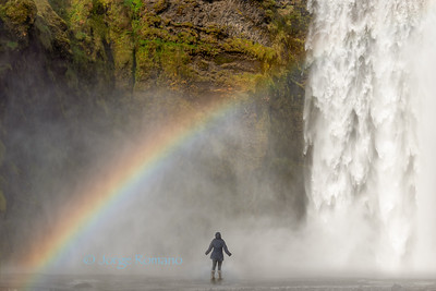 Adventurous woman standing very close to iconic Skogafoss waterfall with rainbow, Southern Iceland
