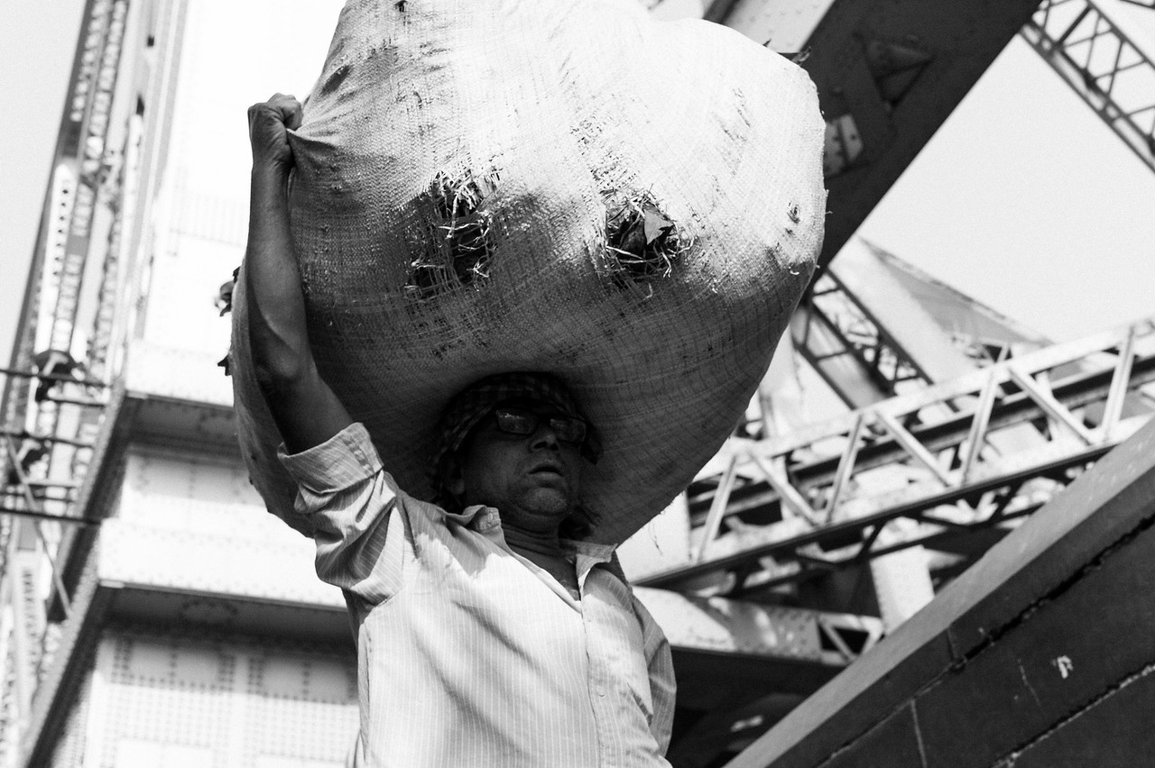 Carrying a load of flowers to the Howrah Flower Market. Kolkata. Leica M9, 50mm.