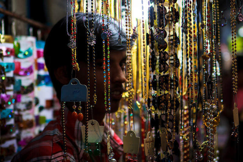 Stealing a Glance: A cheap jewellery hawker steals a quick glance from behind his wares on display at the Market Building complex in Bhubaneswar