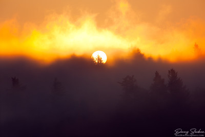 The sun rises through a foggy atmosphere above some nearby ridges.
