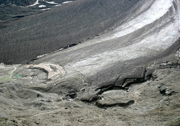 Hikers coming off the southern end of the Pasterze Glacier - adjacent to an glacial pool - Hohe Tauern National Park