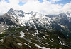 From Edelweiss-Spitze - beyond the Grossglockner High Alpine Road (circling the Fuscher Tori),meandering 30 mi. (48 km) over the Eastern Alps - up to Sonnenwelleck, rising to 10,699 ft. (3,261 m) - and Fuscherkarkoph, rising to 10,929 ft. (3,331 m), both peaks both peaks far right - Hohe Tauern National Park