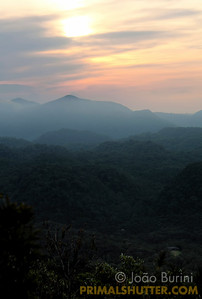 Foggy sunset with mountains in the distance, from a high lookout in Intervales State Park, Brazil. South-east atlantic forest reserve, UNESCO World Heritage Site.