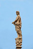 Statue atop a spire, atop the Milan Cathedral