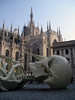 From the shaded Calamita Cosmica (Cosmic Magnet) by Gino De Dominicis - laying in the Piazza del Duoma (Cathedral Square) - with the sunlit Milan Cathedral behind