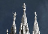 The sunlit statues atop the spires of the Milan Cathedral