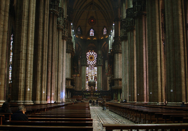 Beyond the pillars along the main nave, past the crossing, to the high altar and twin pulpits at the chancel, with the stained glass at the apse beyond - Milan Cathedral