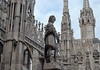 Gargoyle and sculpted statue among the spires of the Milan Cathedral