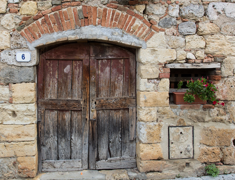 Close-up of medieval house and ancient wooden door, Monteriggioni, Italy