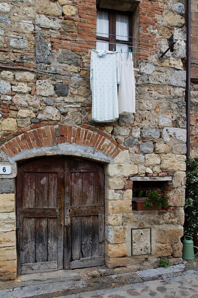 Front of medieval house with clothes hanging outside a window, Monteriggioni, Italy