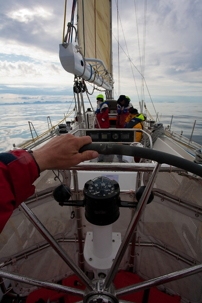 At the helm with the Lofoten Islands on the horizon.