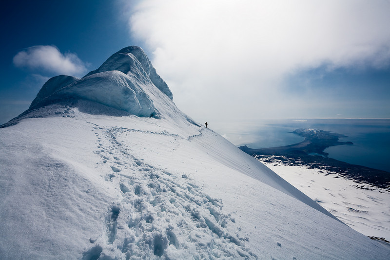 Climber below a lesser summit on the crater ridge of Beerenberg, Jan Mayen.