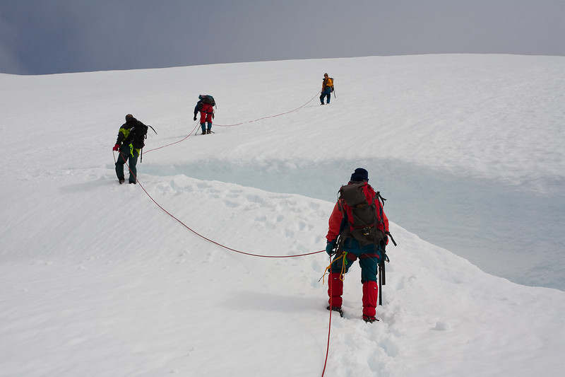 Crossing a crevasse just below the summit ridge of Beerenberg. Jan Mayen