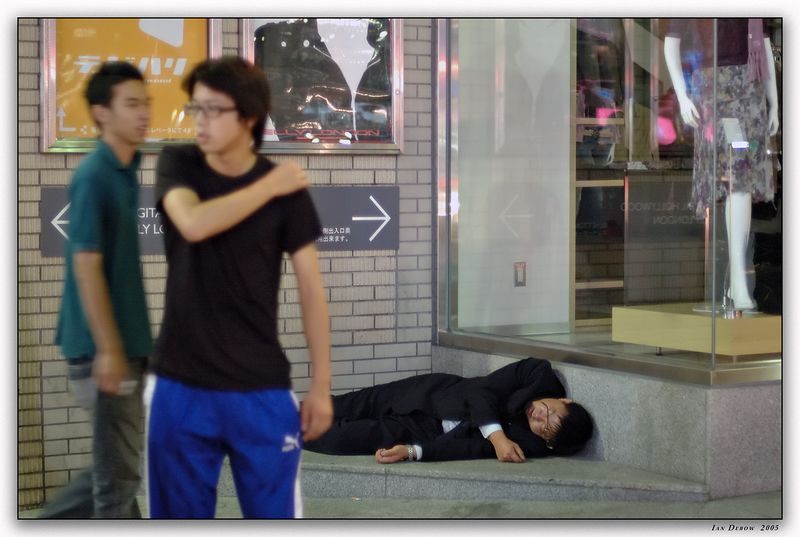 Not an uncommon scene around party areas in Japan.  More than likely someone will come along and help this man into a taxi.  More than likely he'll wake up with both his watch and his wallet on him.