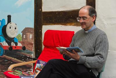 The Revd Dr John White reads Thomas the Tank Engine to visiting children
