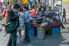 A man takes a bite of street food as he walks by a table of hats for sale on a sidewalk in Seoul's Insa-dong neighborhood. (Jongno-gu, Seoul, KR - 03/27/13, 3:29:57 PM)