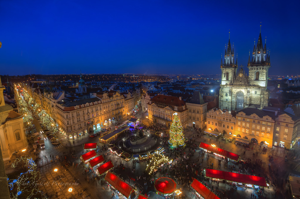 The view from the Old Town Hall Tower, built in 1338 and harboring the famous astronomical clock, in Old Town Square.  The dual spired Cathedral is Tyn Church.  The colorful red tented marketplace below opens for Christmas each year, and is full warm breads, candy and other Christmas treats.