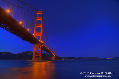 Orange And Blue San Francisco ©  2010 Colleen M. Griffith. All Rights Reserved.  This material may not be published, broadcast, modified, or redistributed in any way without written agreement with the creator.  This image is registered with the US Copyright Office. www.colleenmgriffith.com www.facebook.com/colleen.griffith  Golden Gate bridge at sunset.  The fading blue light of twilight, combined with the red hues of the bridge and the white city lights in the distant background, creates an almost patriotic feel to the city.  You can see more of my San Francisco photos, by going to my San Francisco gallery: www.colleenmgriffith.com/Galleries/San-Francisco/San-Francisco