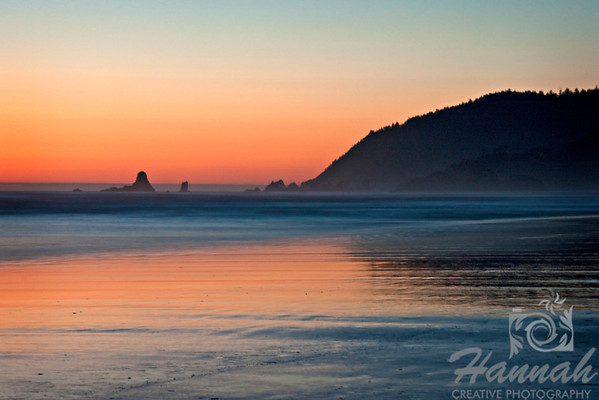 Stretch of Cannon Beach in the Oregon Coast with the silhouette view of the rock formations and Indian Beach at the distance ... Shot at dusk  © Copyright Hannah Pastrana Prieto