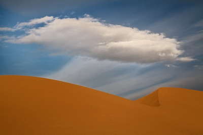A lone cloud hovers over the Ibex Dunes, Death Valley.