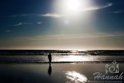 View of the beach with a silhouette of a boy walking.  Creative lens flare can be seen.  Backlighting shot at Cannon Beach, Oregon Coast.  © Copyright Hannah Pastrana Prieto