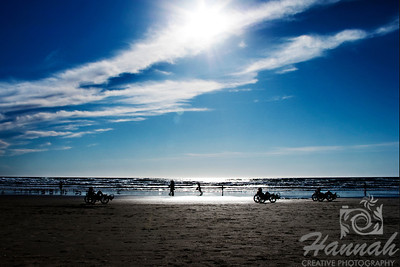 View of the beach with silhouette of people riding their tricycles.  Creative lens flare can be seen.  Backlighting shot at Cannon Beach, Oregon Coast.  © Copyright Hannah Pastrana Prieto