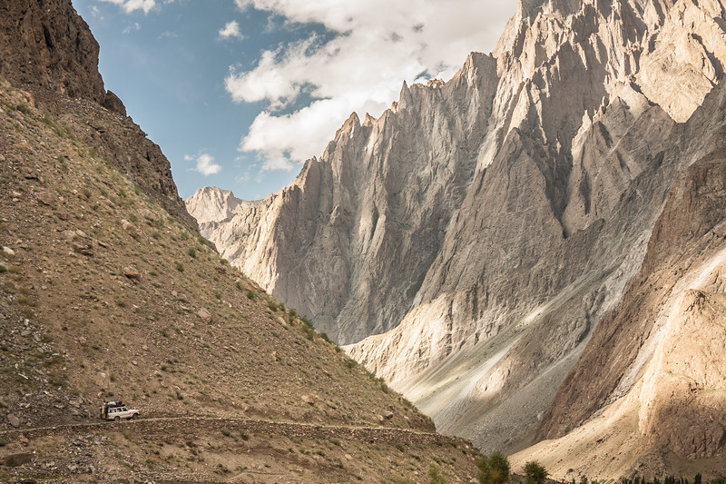A jeep is dwarfed by the jagged peaks of the Hushe valley, Baltistan