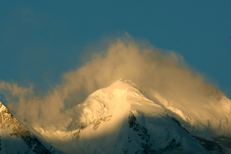 Rakaposhi's summit at sunrise, covered by a cloud cap