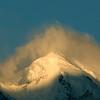 Rakaposhi's summit at sunrise, covered by a cloud cap