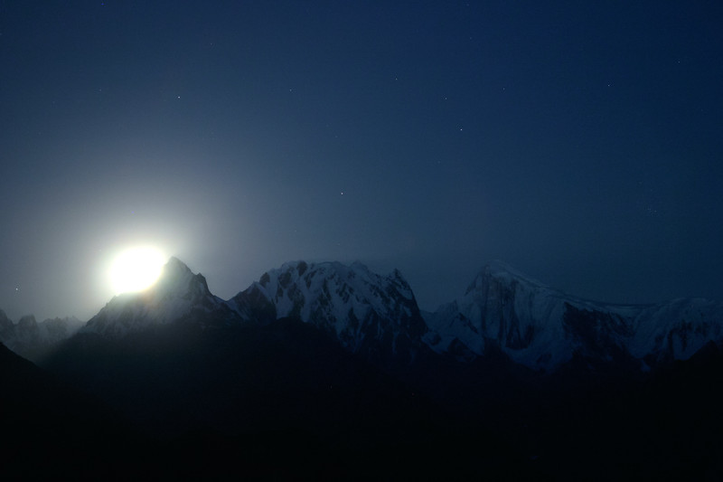 The full moon rises over a peak in Hunza