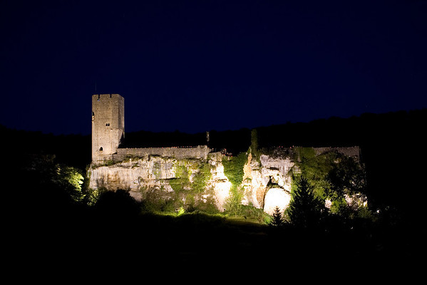 Chateau de Gavaudun floodlit at night.