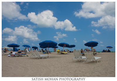Miami Beach, Miami, Florida  Blue umbrellas contrast with the puffy white clouds...