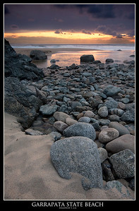 A rock strewn beach leads to the sunset at Garrapata State Beach.