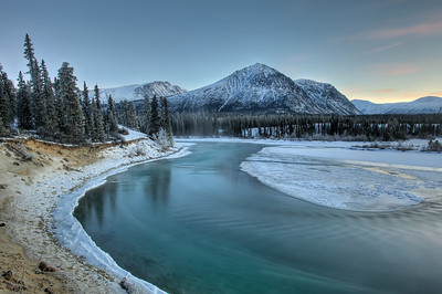 The clear, clean waters of the Takhini River in late fall. The land is freezing and the river will follow shortly. Mt. Vanier in background. Kusawa Lake Territorial Park. Yukon Territory, Canada.