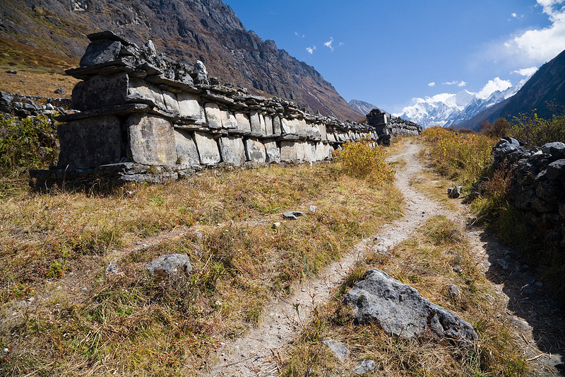 A mani wall above Langtang Village. A mani wall is comprised of hundreds of mani stones in which Buddhist prayers have been incribed. / Langtang Himal, Nepal