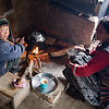 A boy and his mother warming themselves by the fire and drinking chai, a sweet Nepali milk tea. / Langtang Himal, Nepal