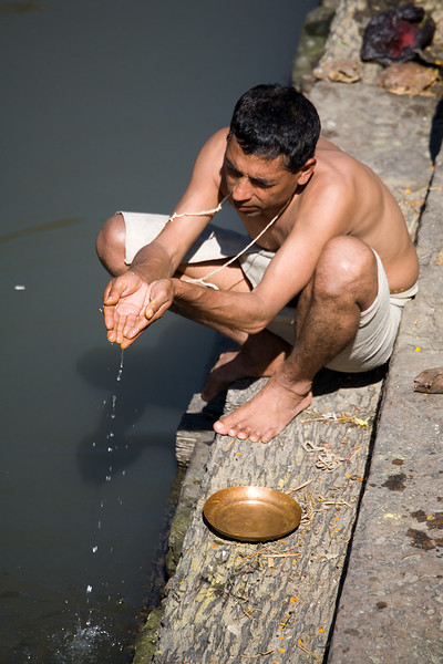 A Hindu priest making a puja, or offering, in the sacred waters of the Bagmati River at Pashupatinath in Kathmandu. / Kathmandu, Nepal