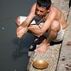 A Hindu priest making a puja, or offering, in the sacred waters of the Bagmati River at Pashupatinath in Kathmandu. / Kathmandu, Nepal