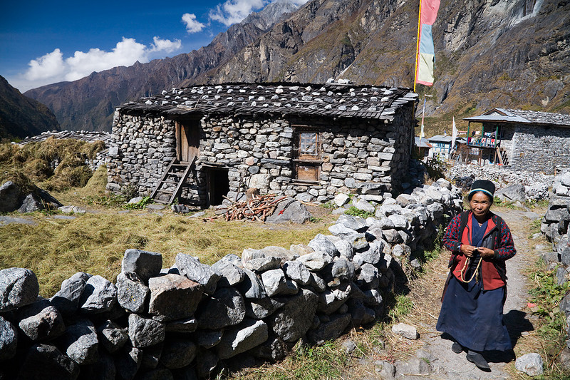 A woman with prayer beads walking through the village of Langtang. / Langtang Himal, Nepal